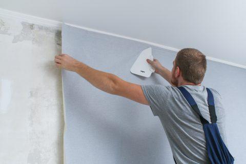 Homme qui pose du papier peint sur un mur