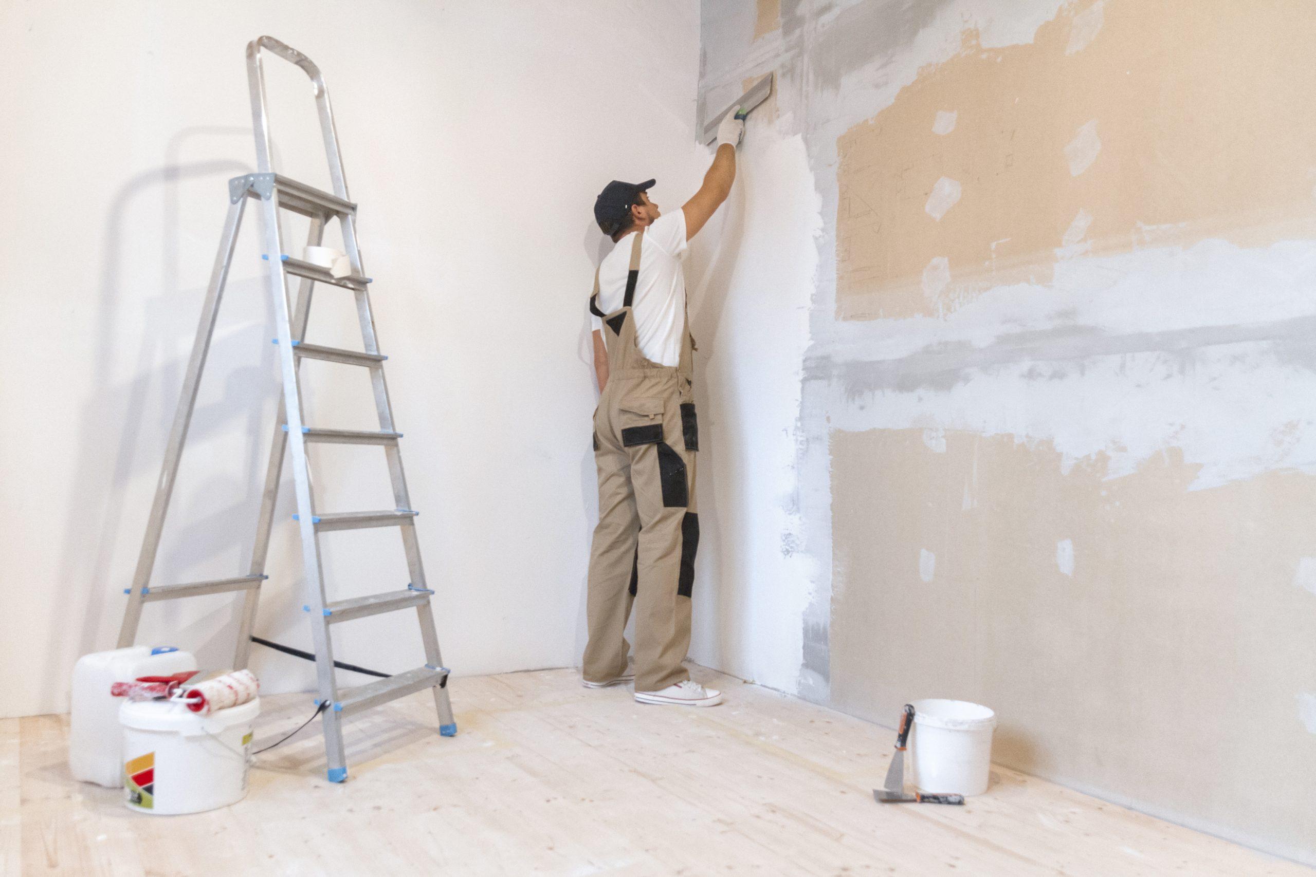 Platrier qui met à niveau un mur