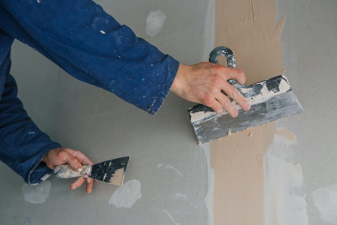 Artisan peintre rebouche une fissure dans un mur
