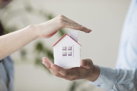 Deux mains qui protègent une maison