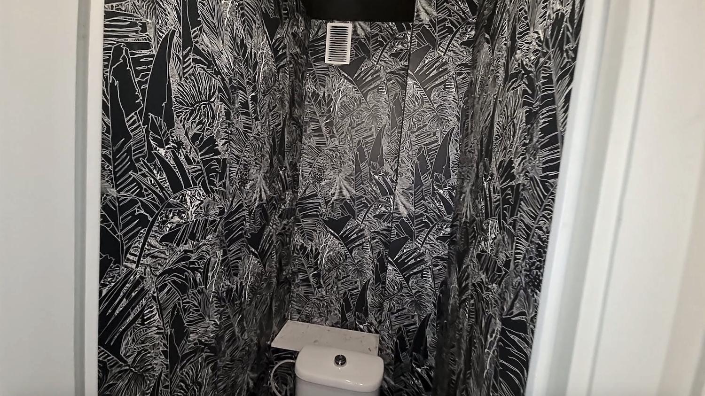 Toilettes tapissé avec un papier peint blanc noir motif jungle